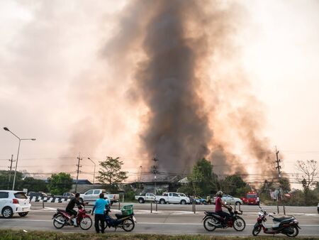 misadventure: Lamphun, Thailand - April 9, 2016: During the morning April 9, 2016. Fire recycling warehouse, causing a large flame and smoke in the air is very hot days. Firemen rush to help prevent the spread of fire , In Thailand.