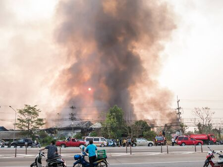 misadventure: Lamphun, Thailand - April 9, 2016:Fire recycling warehouse, causing a large flame and smoke in the air is very hot days. Firemen rush to help prevent the spread of fire , In Thailand.