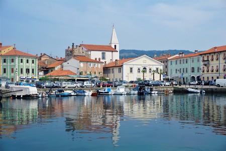 Pequeña plaza con iglesia y autos en el puerto de Izola Foto de archivo - 93911742