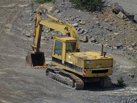 Yellow power shovel in the dirt spotted in a quarry