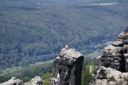 Man and womand sitting on a sandstone rock in the Schrammstein region of Saxon Switzerland, Germany