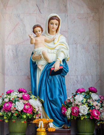 stood: Virgin Mary statue stood among the flowers.