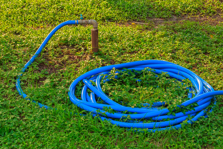Blue rubber hose with faucet on the green lawn