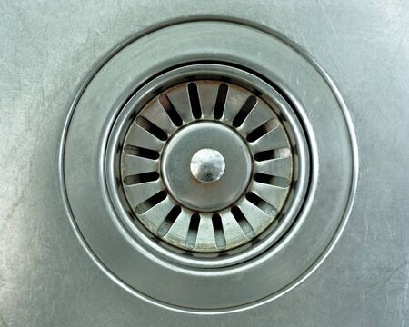 sink drain: close up a drain hole metallic kitchen sink Stock Photo
