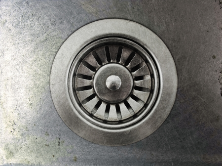 close up a drain hole metallic kitchen sink photo