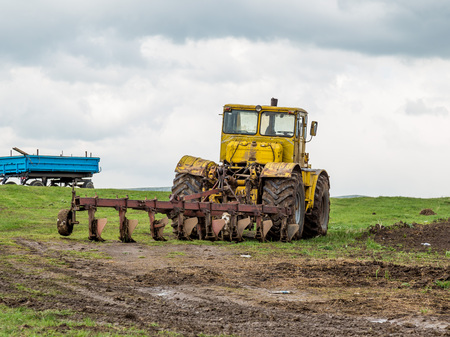 The tractor plows the land in the fields in the spring.