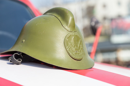 green historical helmet fireman, on the hood of the machine. Stock Photo