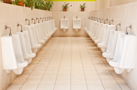 white porcelain urinals in public toilets photo
