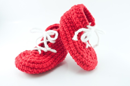 A pair of knitted, bright red baby booties Zdjęcie Seryjne