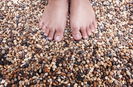 young woman foot of standing on colorful natural stones. with space for text
