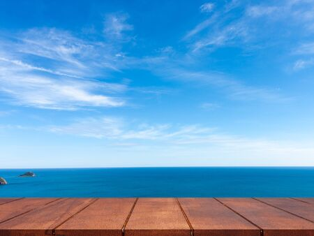 Empty wooden table on blue sky with seascape background. Stock Photo