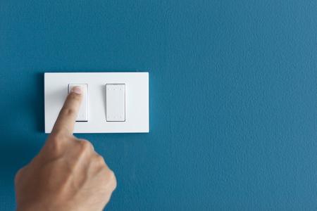 Een vinger die de verlichting aanzet, gaat ruw aan op een blauwe donkere muur. Lege ruimte voor tekst uw Stockfoto
