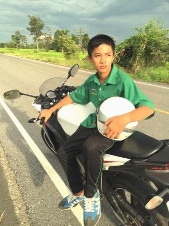 sit: Boy sit on motorbike sunny