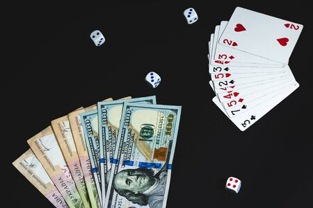 Money, dices and cards on a black background. View from above. large notes dollars and hryvnia Stockfoto