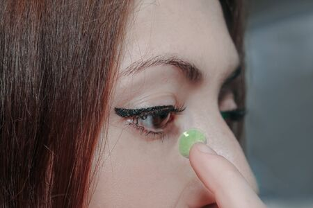 girl with colored lenses for changing eye color. one eye with a green lens that changes color. green contact lens