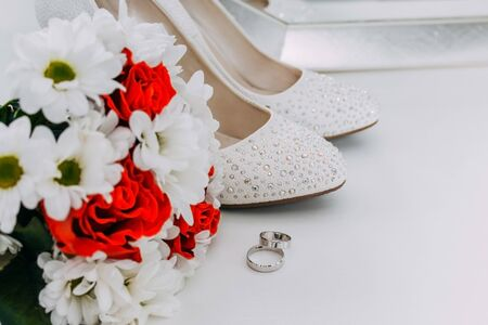 Wedding decor, details of the morning of the bride. White shoes in rhinestones and wedding rings