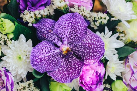 A bouquet of flowers in purple tones with a tiger orchid in the center. Close view