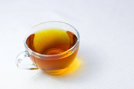 cup of tea on the table on a white tablecloth. Invigorating tea