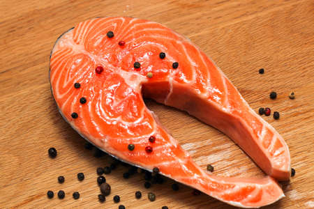 Fresh salmon steak on a wooden board with spices and pepper. Preparing for cooking.