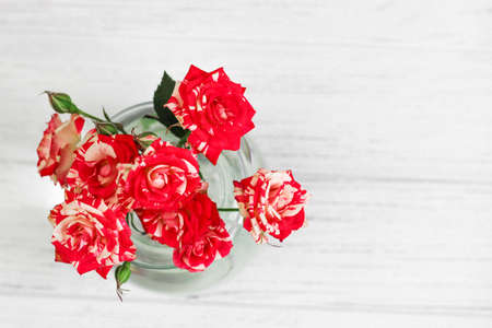 Bouquet of red roses in a vase on a white background from boards.