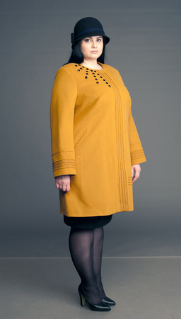 large woman: yellow coat, yellow womens coat, yellow spring coat, girl in a hat, lady, lady in a hat, ladies hat, hat, girl with a bag, full girl, big woman, large woman, womens clothing of the big size Stock Photo