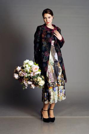 overcoat: woman with a bouquet, big bouquet, coat, fashionable coat, bright coat, autumn womens coat, womens coat, light overcoat Stock Photo