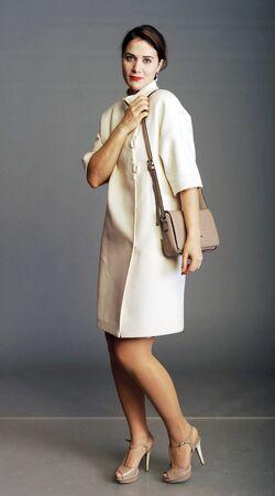 bata blanca: capa, capa blanca, chica en un abrigo blanco, bolso de las señoras, bolso, mujer con un bolso, embrague, chica con un embrague Foto de archivo