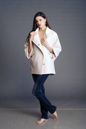 white coat: coat, white coat, girl in a white coat, ladies handbag, handbag, woman with a handbag, clutch, girl with a clutch Stock Photo