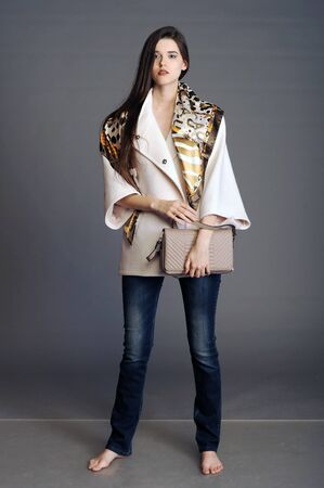 bata blanca: capa, capa blanca, chica en un abrigo blanco, bolso de las se�oras, bolso, mujer con un bolso, embrague, chica con un embrague Foto de archivo