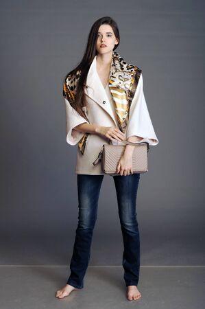 bata blanca: coat, white coat, girl in a white coat, ladies handbag, handbag, woman with a handbag, clutch, girl with a clutch Foto de archivo