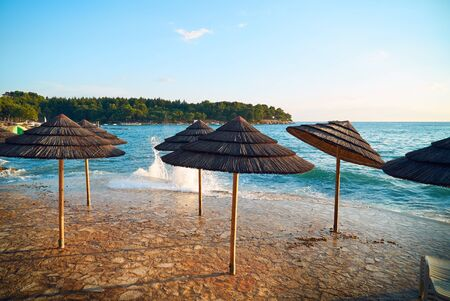 Umbrellas from the sun on the shore of the seething sea.
