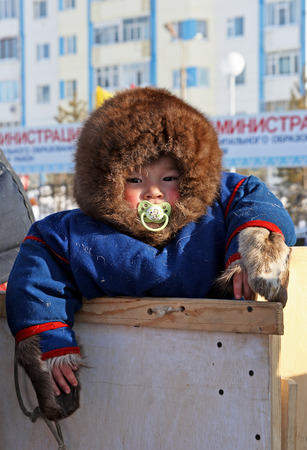 siberia: Nadym, Russia - on March 14, 2009: The child of the people Nenets in national clothes on a traditional holiday Day of the reindeer breeder. The Nenets - natives of the Russian North