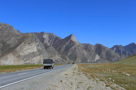 The road in Mountains Altai in the spring afternoon and cars photo
