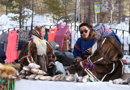 breeder: NADYM, RUSSIA - MARCH 14, 2015: Nenets trade in meat of deer and fish on a traditional holiday Day of the reindeer breeder. Nenets - aboriginals of the Russian North Editorial