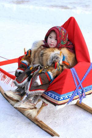 breeder: NADYM, RUSSIA - MARCH 14, 2015: the girl the Nenets woman in fur clothes sits in a sledge during a traditional holiday Day of the reindeer breeder. Nenets - aboriginals of the Russian North