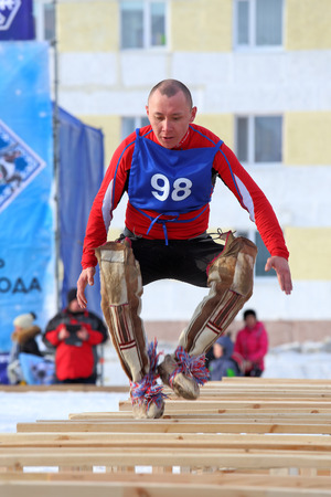 breeder: NADYM, RUSSIA - MARCH 14, 2015: competitions in the Nenets national sport - jumps through sledge on a traditional holiday Day of the reindeer breeder. Nenets - aboriginals of the Russian North