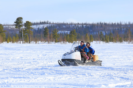 breeders: NADYM, RUSSIA - MARCH 14, 2015: Two young men in the Nenets national clothes ride a snowmobile during a holiday Day of reindeer breeders. Nenets - aboriginals of the Russian North