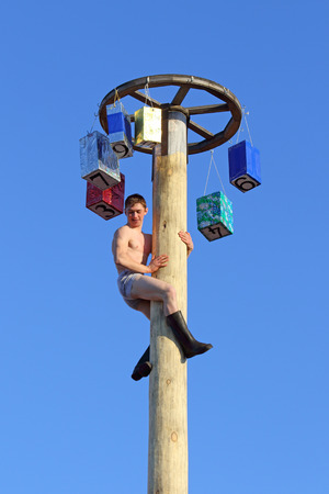 belokurikha: BELOKURIKHA, RUSSIA - MARCH 12, 2016: Maslenitsa is a Russian religious and folk holiday. The young man on a column with prizes