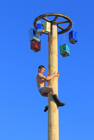 maslenitsa: BELOKURIKHA, RUSSIA - MARCH 12, 2016: Maslenitsa is a Russian religious and folk holiday. The young man on a column with prizes