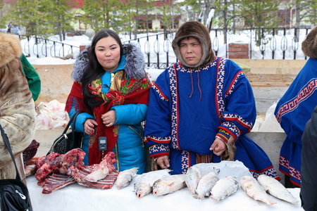 herder: NADYM, RUSSIA - MARCH 14, 2015: A man and a woman Nenets sell frozen fish and venison during a holiday day of the reindeer herder. Nenets - aboriginals of the Russian North