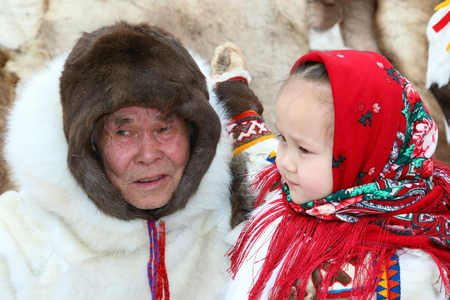 NADYM, RUSSIA - MARCH 04, 2017: Granddaughter and grandpa Nenets people in national clothes on a traditional holiday Day of the reindeer breeder. Nenets - aboriginals of the Russian North
