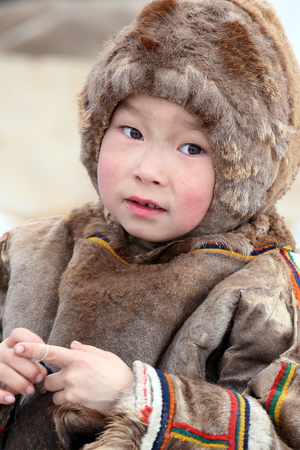 """NADYM, RUSSIA - MARCH 05, 2017: Boy reindeer breeder Nenets in national clothes on a traditional holiday """"Day of the reindeer breeder"""". Nenets - aboriginals of the Russian North"""