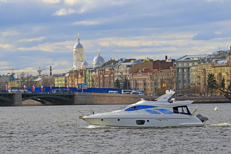 Saint Petersburg, RUSSIA - MAY 06, 2017: Motor yacht against the backdrop of historical buildings and the Prince Vladimir Cathedral Editorial