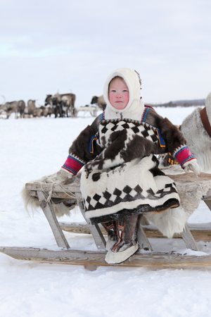 NADYM, RUSSIA — MARCH 04, 2018: Nenets girl in national dress sitting on a sled during the holiday of the reindeer breeder Day. Nenets — aboriginals of the Russian North Publikacyjne