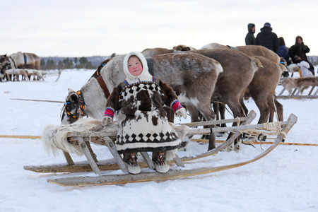 NADYM, RUSSIA — MARCH 04, 2018: Nenets girl in national dress sitting on a sled during the holiday of the reindeer breeder Day. Nenets — aboriginals of the Russian North Redactioneel