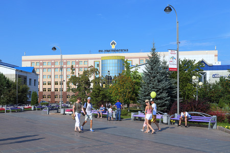 Tyumen, RUSSIA-AUGUST 14, 2018: The having a rest citizens walk on Tsvetnoy Boulevard against the background of the building of the oil-extracting company LLC RN-Uvatneftegaz