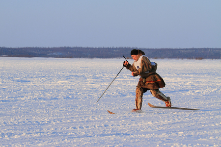 NADYM, RUSSIA - FEBRUARY 26, 2012: Nenets man runs on skis during a national holiday. Nenets - aboriginals of the Russian North