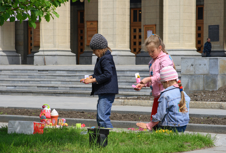 Novosibirsk, RUSSIA-MAY 27, 2008: Children playing on the lawn near the Opera and ballet theatre