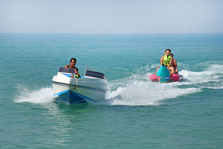 PATTAYA, THAILAND-JANUARY 02, 2014: Tourists have fun riding on the tropical sea in Southeast Asia