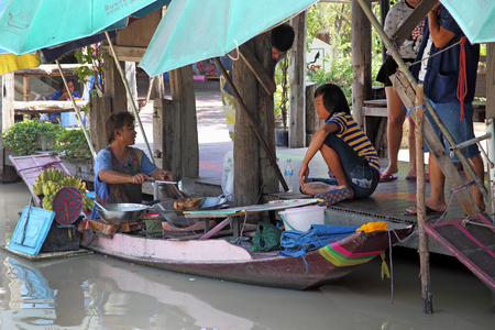 PATTAYA, THAILAND-DECEMBER 29, 2013: Man cooking in a boat on a floating market